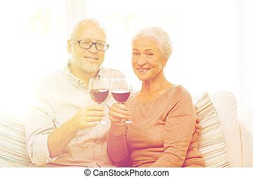 Una pareja feliz con vasos de vino tinto