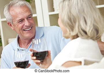 Una pareja feliz de ancianos bebiendo vino en casa