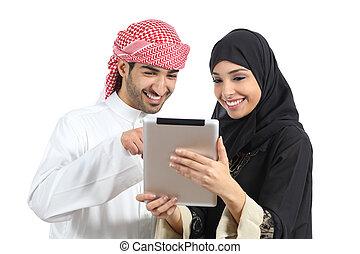 Una pareja feliz de Arabia Saudí mirando a un lector de tabletas