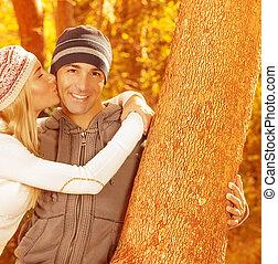 Una pareja feliz en el parque de otoño