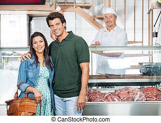 Una pareja feliz en la carnicería