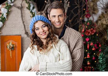 Una pareja feliz en la tienda de Navidad