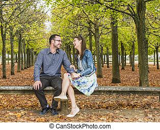 Una pareja feliz en un parque en otoño