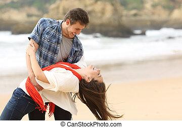 Una pareja feliz enamorada bromeando en la playa
