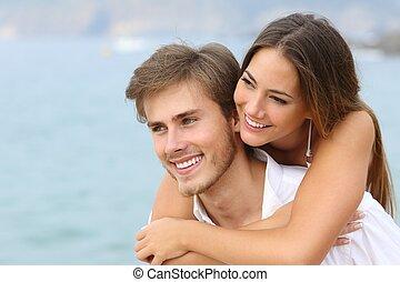 Una pareja feliz enamorada con una sonrisa perfecta en la playa