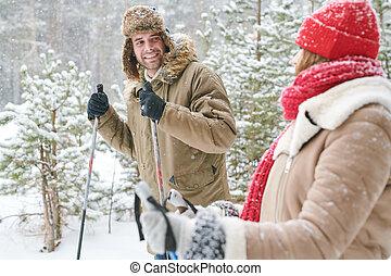 Una pareja feliz esquiando en el bosque