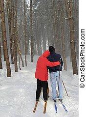 Una pareja feliz esquiando en el campo