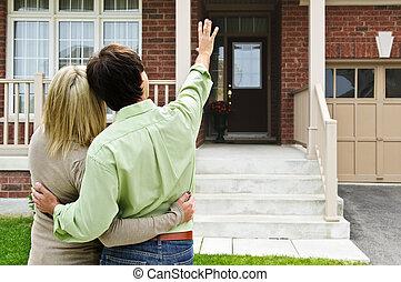 Una pareja feliz frente a casa