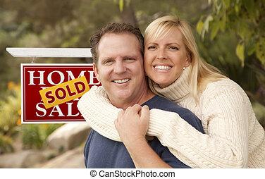 Una pareja feliz frente a la venta de bienes raíces