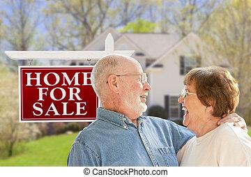 Una pareja feliz frente a la venta