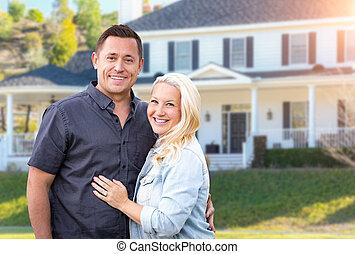 Una pareja feliz frente a una hermosa casa