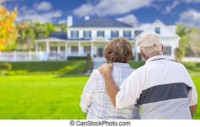 Una pareja feliz mirando al frente de la casa