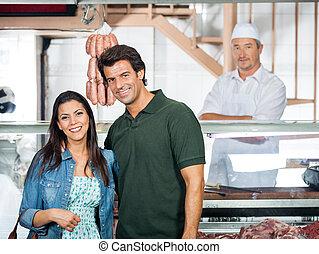 Una pareja feliz parada en la carnicería