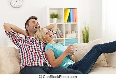 Una pareja feliz relajándose juntos en casa