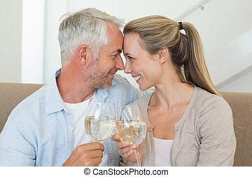 Una pareja feliz sentada en el sofá brindando con vino blanco