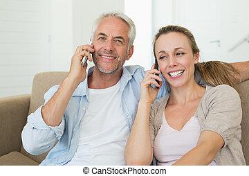 Una pareja feliz sentada en el sofá hablando por teléfono