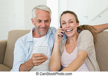 Una pareja feliz sentada en el sofá hablando y enviando mensajes en sus teléfonos en la sala de estar