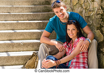 Una pareja feliz sentada en las escaleras sonriendo
