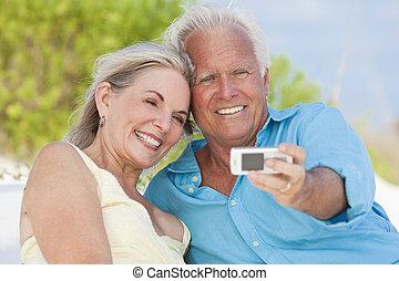 Una pareja feliz tomando fotografías en el celular de la playa