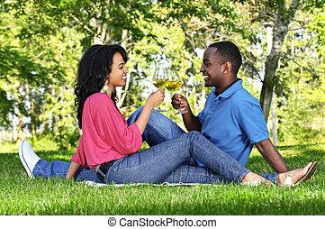 Una pareja feliz tomando vino en el parque