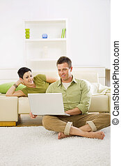 Una pareja feliz usando computadora