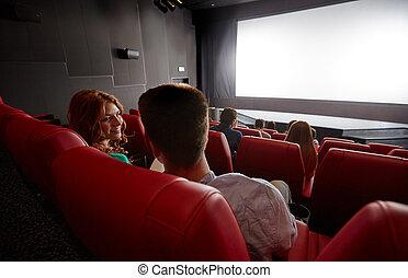 Una pareja feliz viendo películas y hablando en el teatro