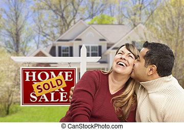 Una pareja frente a la venta de bienes raíces y casa