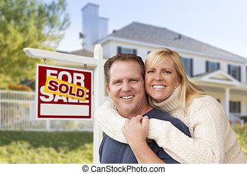 Una pareja frente a una nueva casa y vendió un cartel