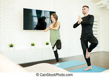 Una pareja haciendo yoga en casa