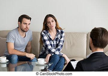 Una pareja infeliz del milenio hablando con un psicólogo sentado en el sofá