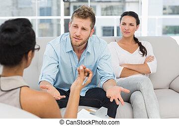 Una pareja infeliz en la sesión de terapia con un hombre hablando con un terapeuta