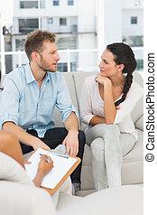 Una pareja infeliz hablando en la sesión de terapia