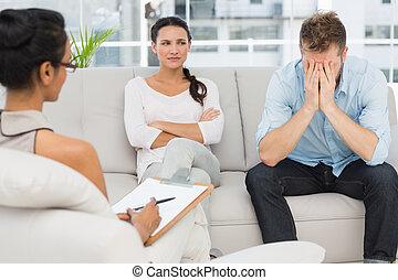 Una pareja infeliz sentada en el sofá en la sesión de terapia