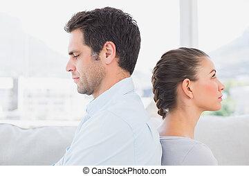 Una pareja infeliz sentada en el sofá