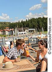Una pareja joven bebiendo cóctel en el bar de la playa