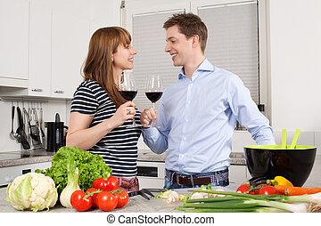 Una pareja joven bebiendo vino en la cocina