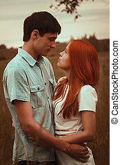 Una pareja joven besándose en el campo de otoño