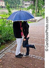 Una pareja joven besándose en el parque bajo el paraguas