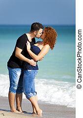 Una pareja joven besándose en la playa.