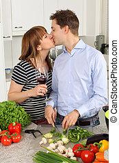 Una pareja joven besándose en su cocina