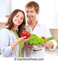 Una pareja joven cocinando comida saludable en casa