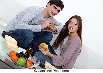Una pareja joven comiendo hamburguesas en el sofá