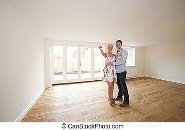Una pareja joven con llaves de un nuevo hogar