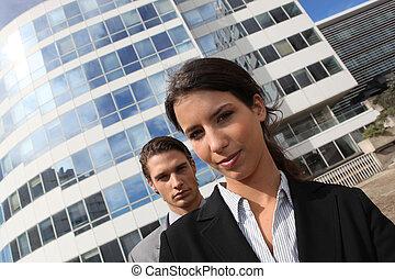 Una pareja joven con trajes parados frente a un edificio de oficinas