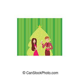 Una pareja joven coquetea y bebe champán cerca del árbol de Navidad