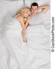 Una pareja joven durmiendo en una cama