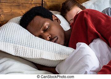 Una pareja joven durmiendo en una cama.
