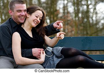 Una pareja joven en un banco divirtiéndose