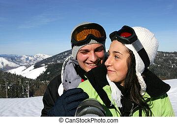 Una pareja joven en una pendiente de esquí