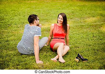 Una pareja joven hablando sobre hierba